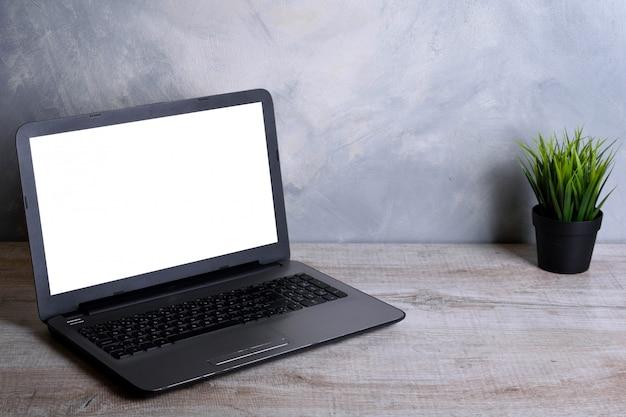 Laptop z pustym ekranem do montażu graficznego. komputer na drewnianym szarym biurku w pokoju biurowym.