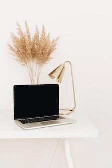 Laptop z pustym ekranem miejsca na kopię na białym stole ze złotą lampą i bukietem trzcin trawy pampasowej