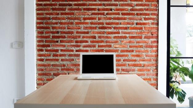 Laptop z pustym ekranem na biurku i ścianą z czerwonej cegły pracuje w domu lub studiuje online