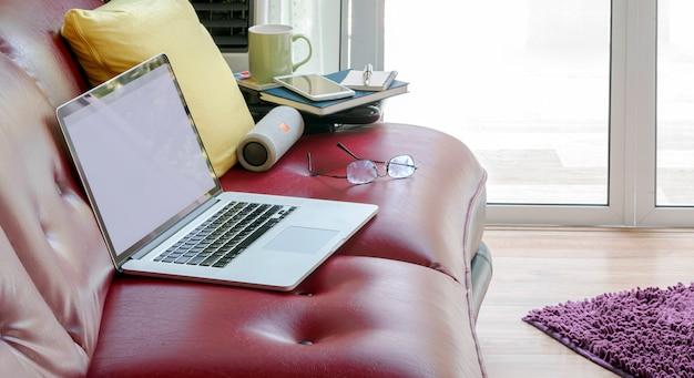 Laptop z pustym ekranem na czerwonej kanapie w salonie.
