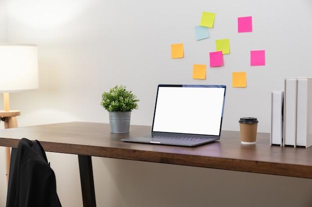 Laptop z pustym ekranem na stole w nowoczesnym biurze.