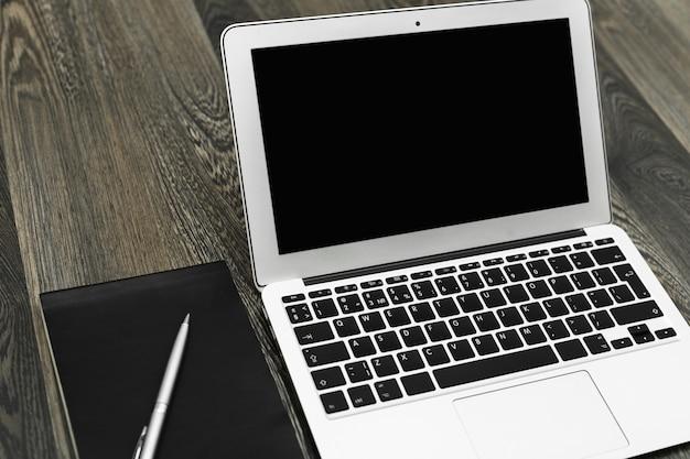 Laptop z pustym ekranem na stole w przemysłowym wnętrzu