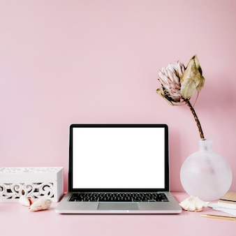 Laptop z pustym ekranem na stole z kwiatem proteus i dekoracją