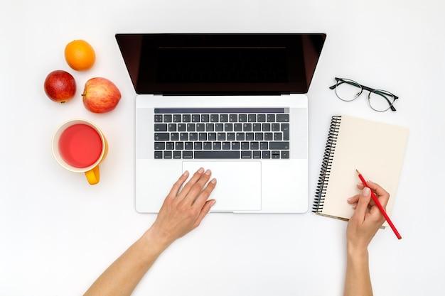 Laptop z pustym ekranem, rękami i akcesoriami na białym tle