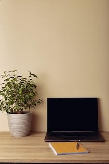 Laptop z pustym ekranem, rośliną doniczkową i żółtym notatnikiem z długopisem.