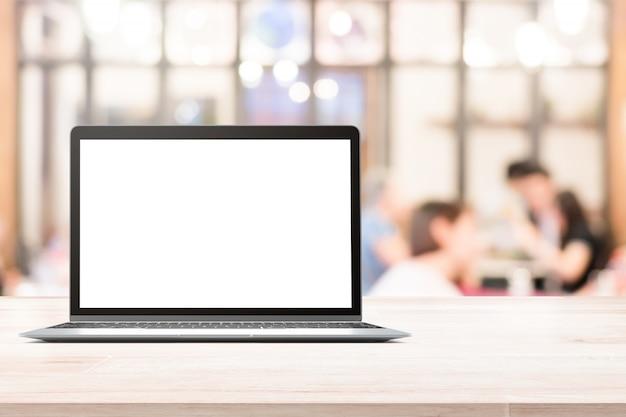 Laptop z pustym ekranem umieszczającym na białym drewnianym stole w zamazanych ludziach