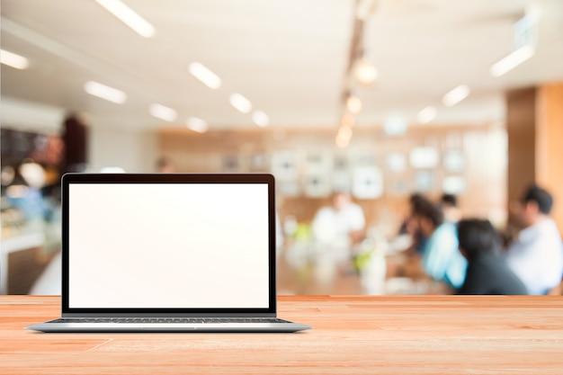 Laptop z pustym ekranem umieszczone na bia? ym drewnianym stole w niewyra? ne osoby w niewyraźne business metting tle dla monta?