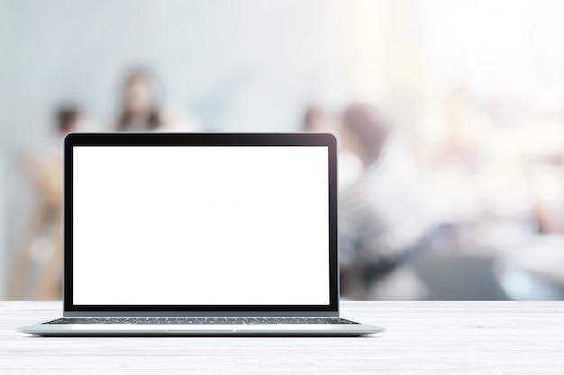 Laptop z pustym ekranem umieszczone na białym drewnianym stole w niewyraźne osoby w kawiarni lub restauracji