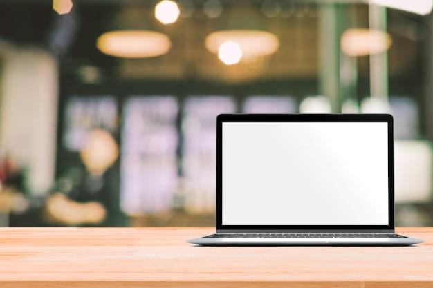 Laptop z pustym ekranem umieszczonym na drewnianym stole w niewyraźne kawiarnia lub restauracja