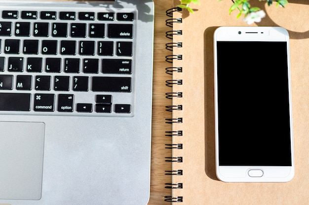 Laptop z smartphone na notatniku, ołówka i kwiatu garnka drzewie na drewnianym tle, odgórnego widoku biura stół.