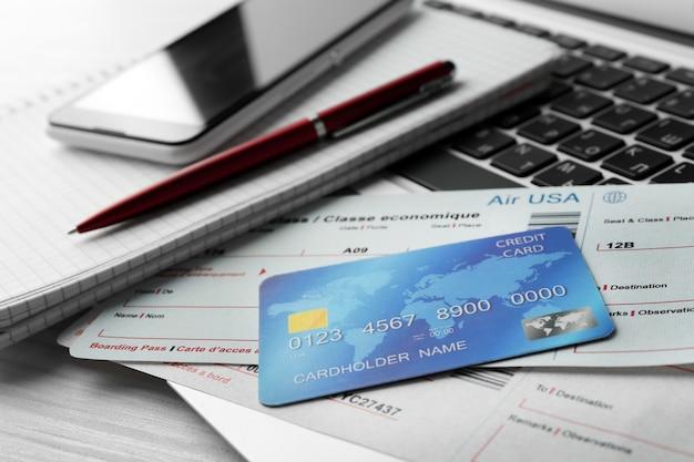 Laptop z telefonem komórkowym, kartą kredytową i biletami lotniczymi na jasnym drewnianym stole