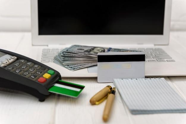 Laptop z terminalem bankowym i banknotami dolarowymi