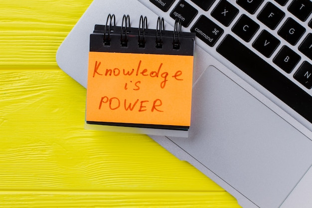 Laptop z widokiem z góry i wiedza to hasło mocy. żółte drewniane tło.