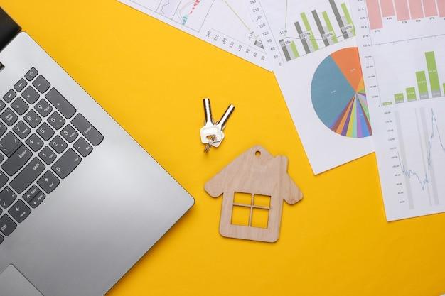 Laptop z wykresami i wykresami, postać domu na żółtym tle. biznesplan, analityka finansowa, statystyki. widok z góry