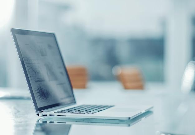 Laptop z wykresem finansowym na ekranie w miejscu pracy