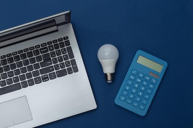 Laptop z żarówką led, kalkulator na klasycznym niebieskim tle. oszczędzać energię. widok z góry