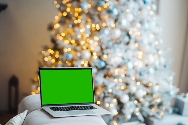 Laptop z zielonym ekranem w pobliżu dekoracji noworocznych
