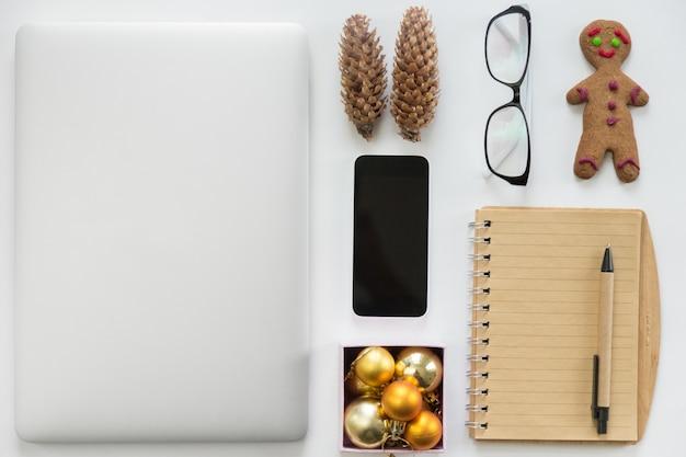 Laptop zamykany, telefon komórkowy, materiały biurowe i ozdoby świąteczne