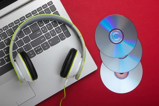 Laptop ze słuchawkami, dyski cd na czerwonej powierzchni