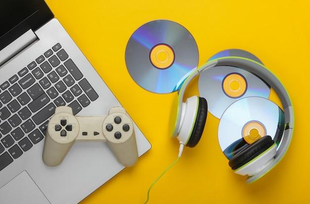 Laptop ze słuchawkami, gamepad, dyski cd na żółtej powierzchni
