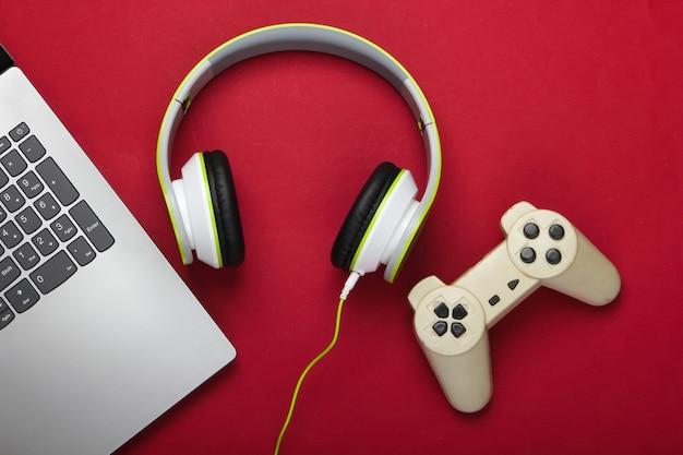 Laptop ze słuchawkami, gamepad na czerwonej powierzchni
