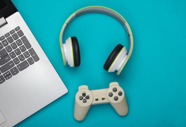 Laptop ze słuchawkami, gamepad na niebieskiej powierzchni