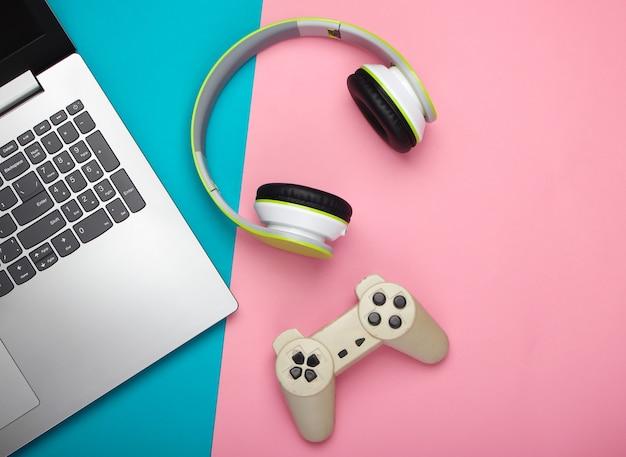 Laptop ze słuchawkami, gamepad na różowo-niebieskiej powierzchni