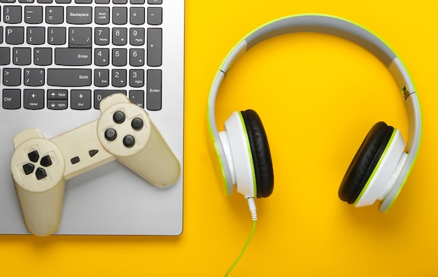 Laptop ze słuchawkami, gamepad na żółtej powierzchni