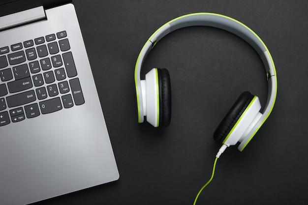 Laptop ze słuchawkami na czarnej powierzchni