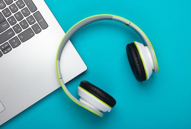 Laptop ze słuchawkami na niebieskiej powierzchni