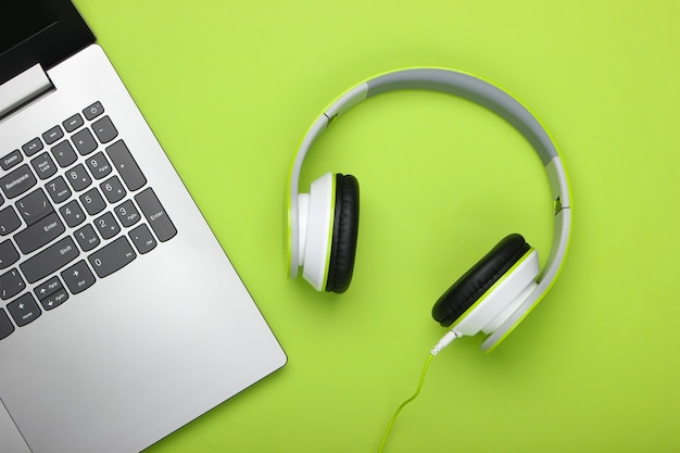 Laptop ze słuchawkami na zielonej powierzchni