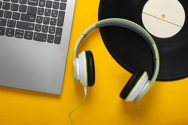 Laptop ze słuchawkami, płyta winylowa na żółtej powierzchni
