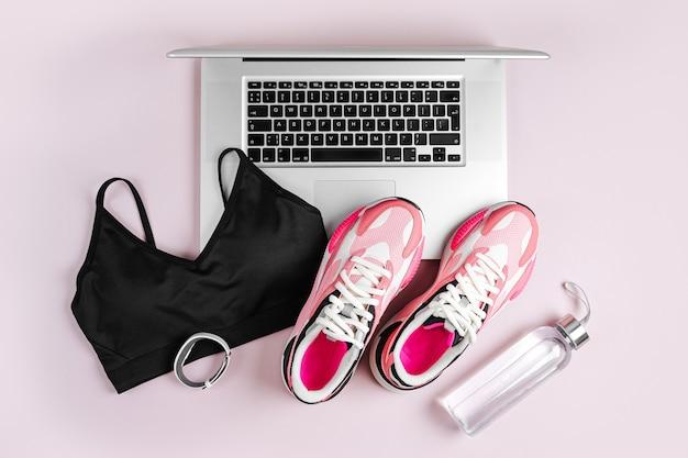 Laptop ze sprzętem sportowym fitness i trampki na różowym tle.