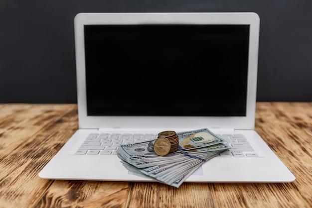 Laptop ze stosem dolarów i złotymi monetami