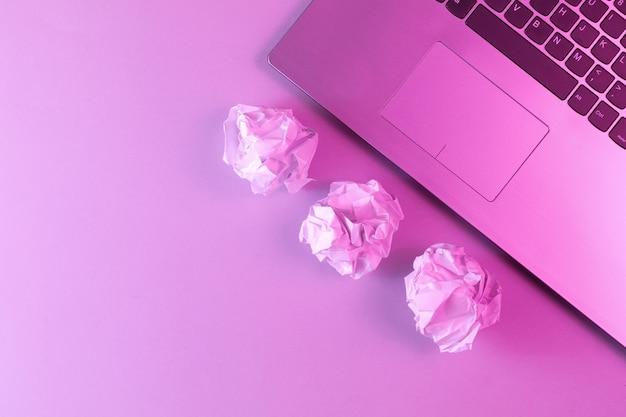 Laptop, zmięte kulki papieru z bliska. holograficzne różowe światło