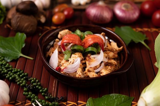 Larb z kurczaka na talerzu z suszonymi chilli, pomidorami, dymką i sałatą