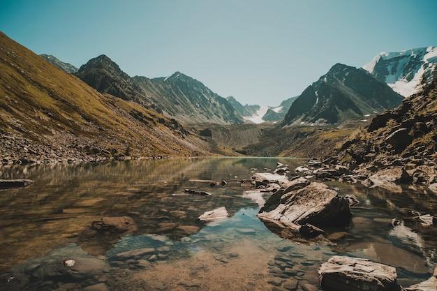 Las ałtaj odbija się nad jeziorem. piękny krajobraz w godzinach porannych z ciepłym tonem. piękny spokojny krajobraz w górach bez ludzi. dzika przyroda na syberii. rosja.