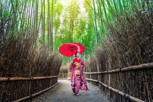Las bambusowy. azjatycka kobieta ubrana w tradycyjne japońskie kimono w bamboo forest w kioto, japonia.