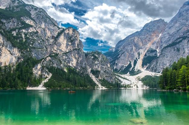 Las i góry odbijają się w szmaragdowych wodach jeziora braies