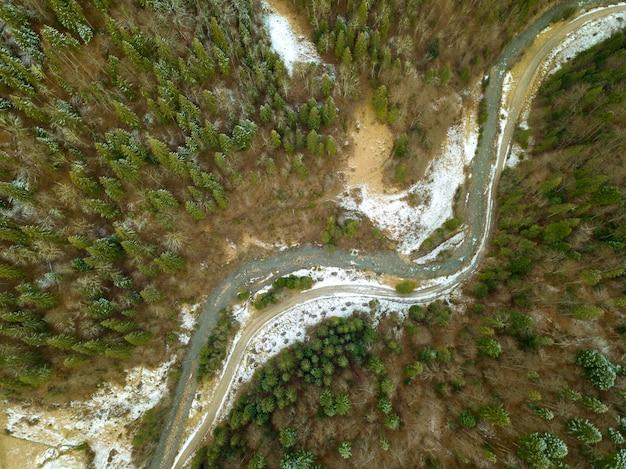 Las świerkowy na początku zimy. mała rzeka. śnieg na ziemi. widok z góry pionowo w dół