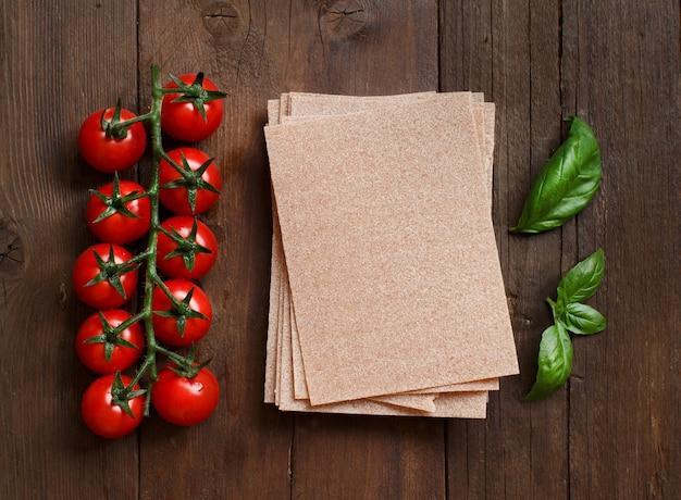 Lasagne pełnoziarnista w arkuszach, pomidory i bazylia na drewnianym stole