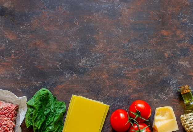 Lasagne, pomidory, mięso mielone i inne składniki. ciemne tło. kuchnia włoska.
