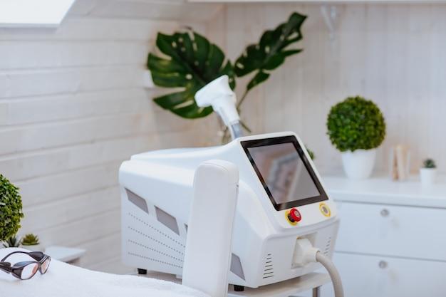 Laserowa depilator w białej obudowie z zielonymi roślinami.