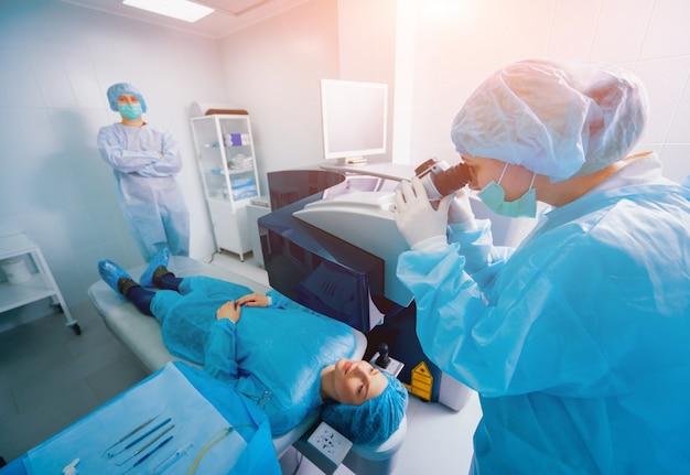 Laserowa korekcja wzroku. pacjent i zespół chirurgów na sali operacyjnej podczas operacji okulistycznej. wziernik powieki. leczenie lasik.