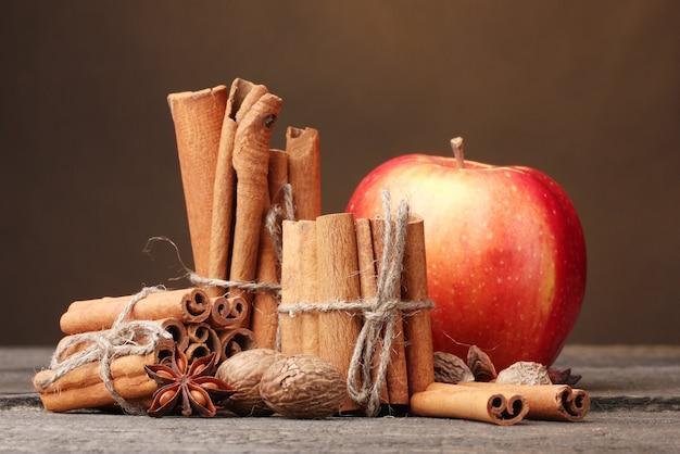 Laski cynamonu, czerwone jabłko, gałka muszkatołowa i anyż na drewnianym stole na brązowym tle
