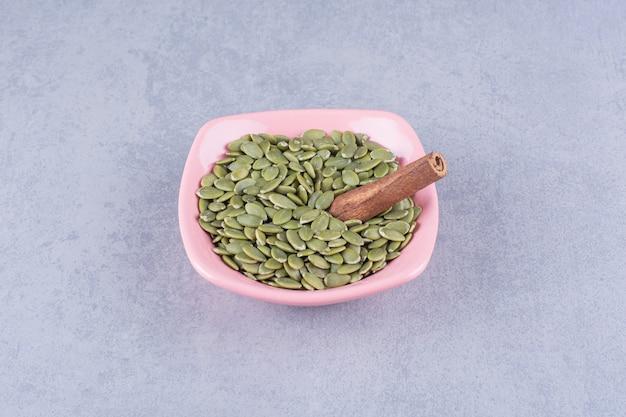 Laski cynamonu i pestki dyni w misce, na marmurze.