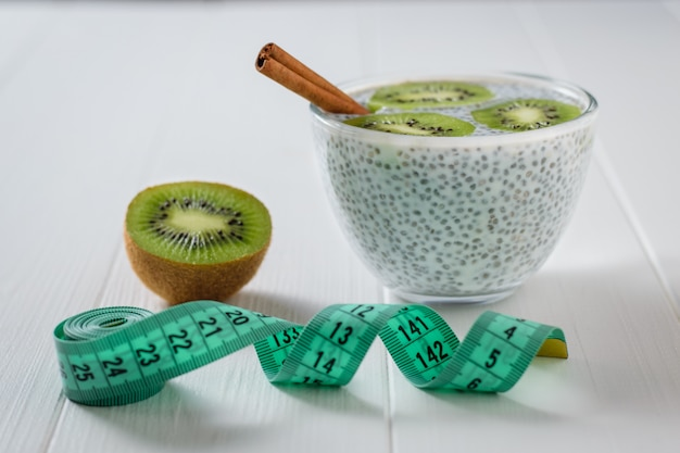 Laski cynamonu, kiwi i szklana miska nasion chia z mlekiem i miarką na białym stole.