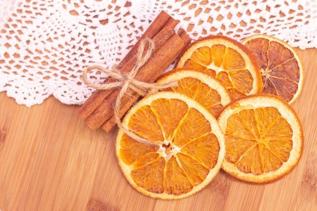 Laski cynamonu, plastry suszonej pomarańczy, na drewnianym. widok z góry. obchody bożego narodzenia i nowego roku. zima i jesień.