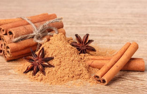 Laski cynamonu, proszek i anyż na drewnianym stole
