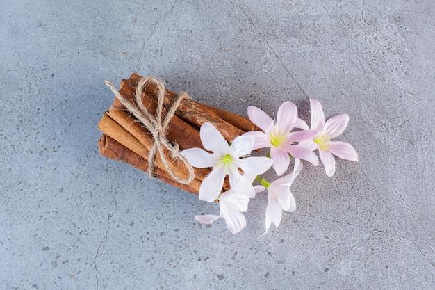 Laski cynamonu w sznurku z białymi i różowymi kwiatami na szarym tle